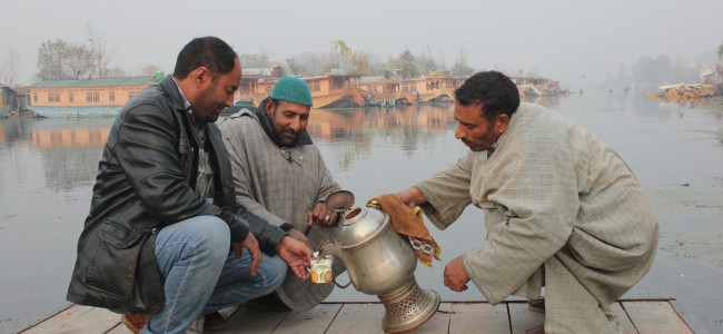 On a chilly day Shikara walas enjoy Noon Chai by the banks of Dal Lake